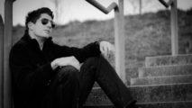 Michael Kratzer mit Sonnenbrille sitzt auf einer Treppe